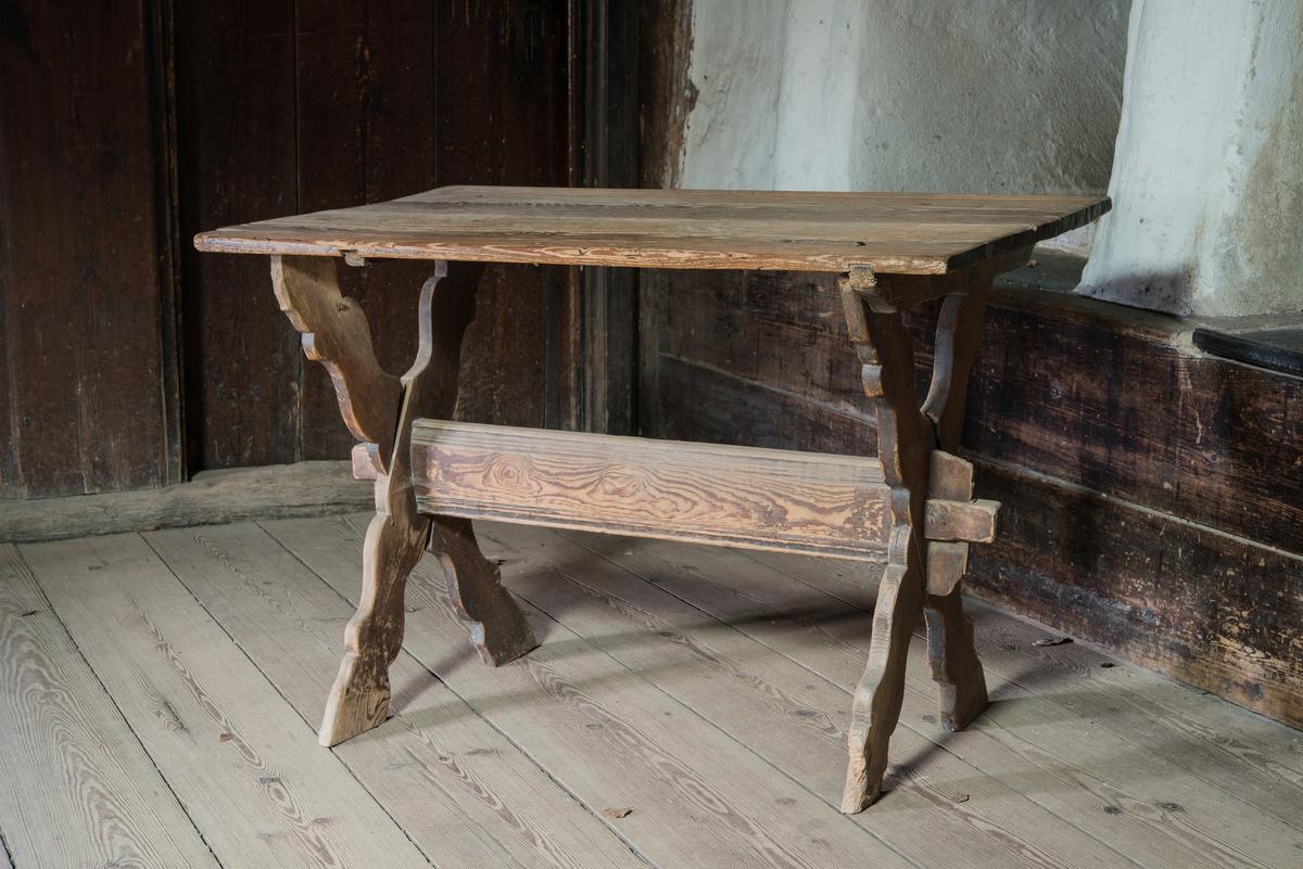 Bord, bockbord, av furu med profilerad kryssbock. Bom med kil och tapp. Skivan omålad. Rester av brun färg på bockställningen.
