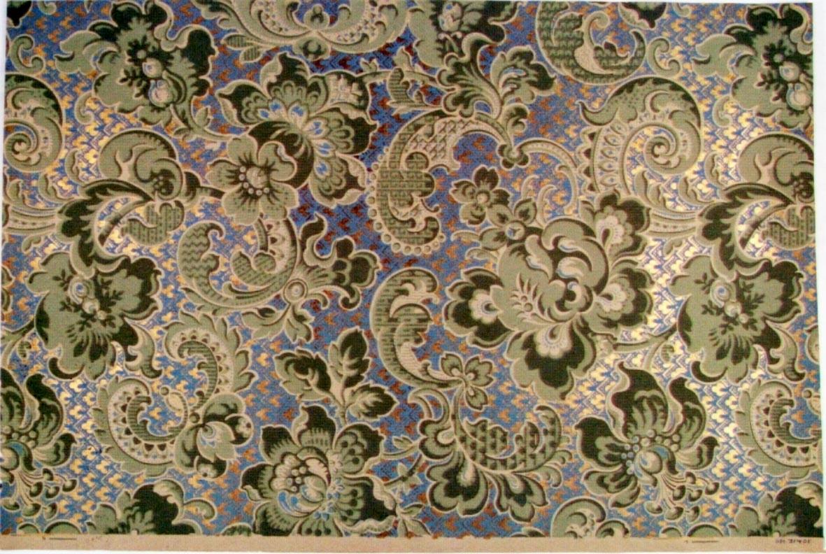 Storfigurigt mönster med fantasiblommor, broskornament och akantusdekor. Tryck i guld, ljusblått, ljusgrönt och olivgrönt. Bakgrunden dekorerad med ett mönster av vinklar, prickar och franska liljan.