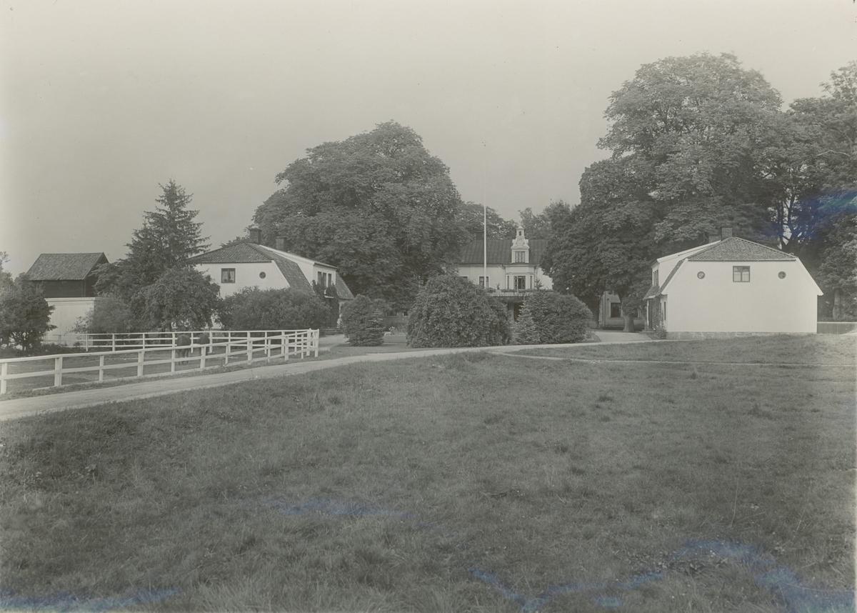 """Forsby herrgård. """"Mangården från söder. Vitputsade träbyggnader. Gamla lönnar och andra parkträd. Längst t.v. syns taket av den gamla spannmålsboden, vilken ligger vid åkanten."""