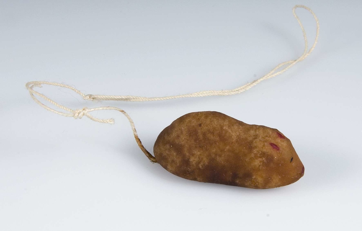 Konfekt av sockermassa i form av ljusbrun mus med svans av snöre som bildar upphägningssögla.Sammanhörande med konfekt  UM16808-UM16832.