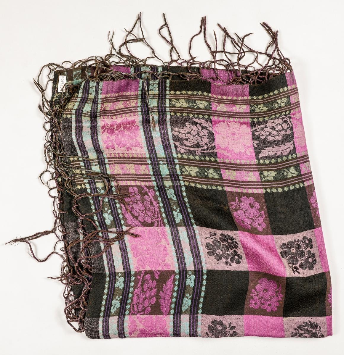 Tørkle i damask, bomull i renning og ull i innslag. Brunt i botn med ruter i rosa, grønt, fiolett og turkis. Falda (tråkla) på to sider, jarekant i dei to andre. Påsydde og knytta frynser i rosa og brunt.