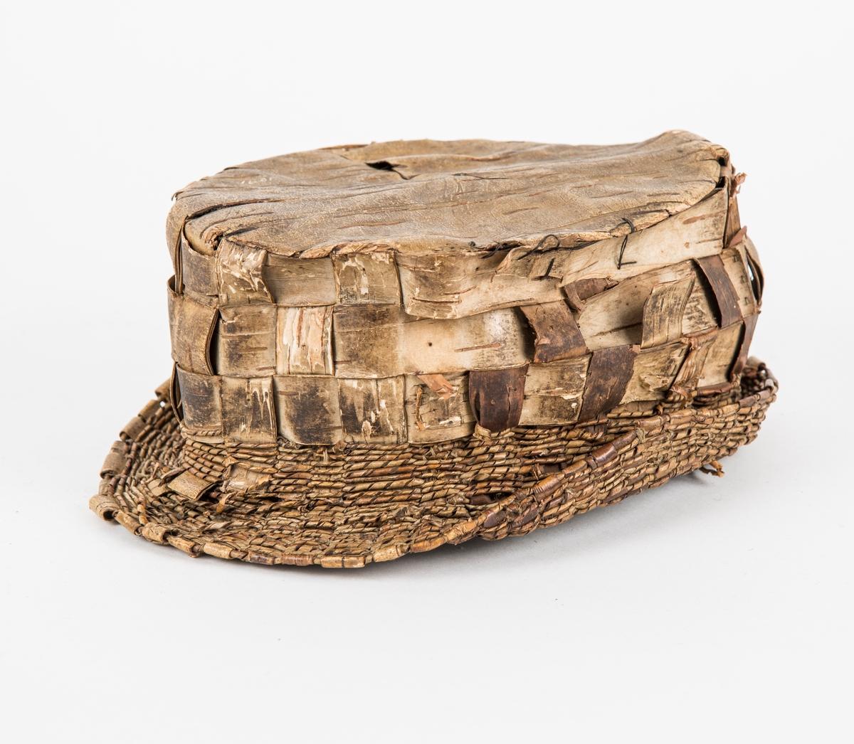 Hatt i bjørkenever. Pullen og bremmen er fletta i like store strimlar. Bremmen er pynta på utsida og innsida med smale snudde strimlar.