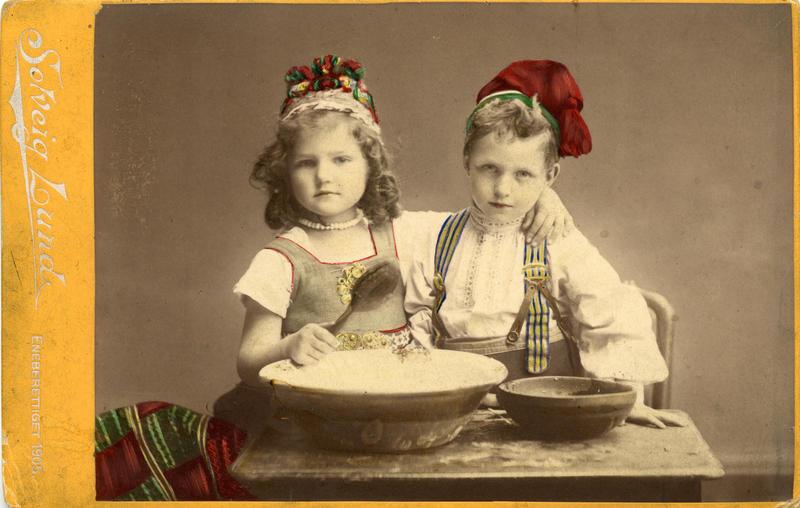 Kolorert studiofotografi av jente og gutt med drakt, sittende ved bord med to treboller, ei sleiv. 1905