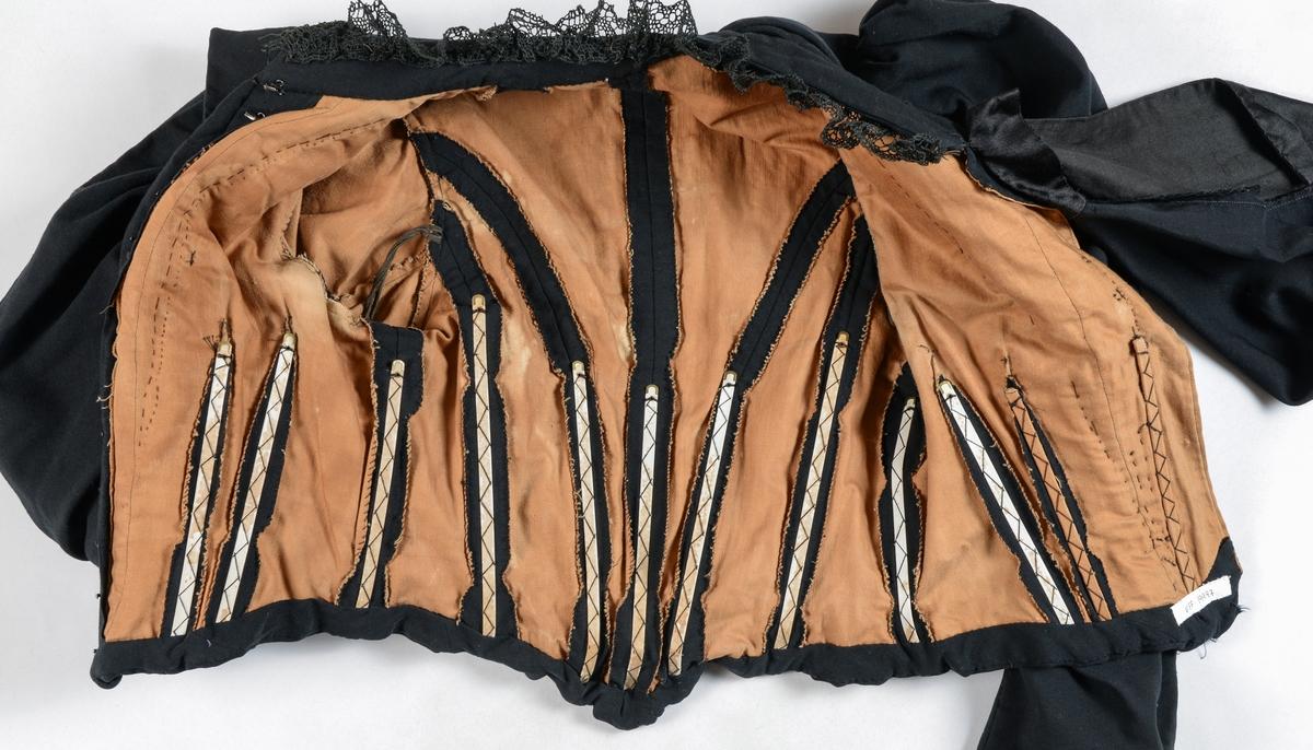 Kjoleliv i svart tynt ulltøy. 13 usynlege hekter og krokar i opninga. Halslinning med svart blondekant. Framstykket har tre folder på kvar side av midten, Innsvinga i livet. Saum midt bak og med to svinga saumar på kvar side. Bakovertrekte skuldersaumar. Rynka erme øverst med stor vidde, smal nederst. 13 spiler i livet. Fóra med lys brunt bomulltøy. Fór og tøy er sydd i saman under eitt med maskin.