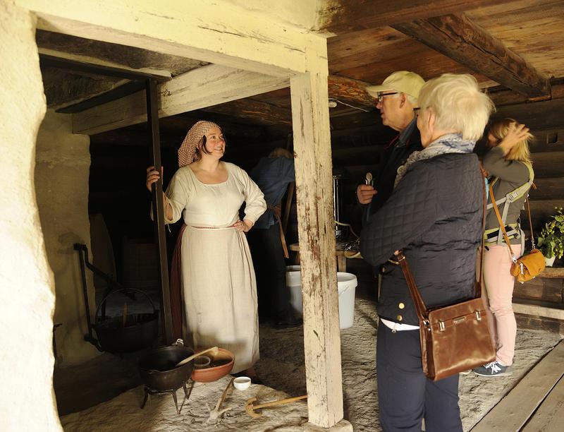 Kvinne med skaut og forkle over stakken lener seg på kanten av en peis hvor det henger ei gryte med grøt, kvinna snakker med to eldre mennesker som besøker museet.