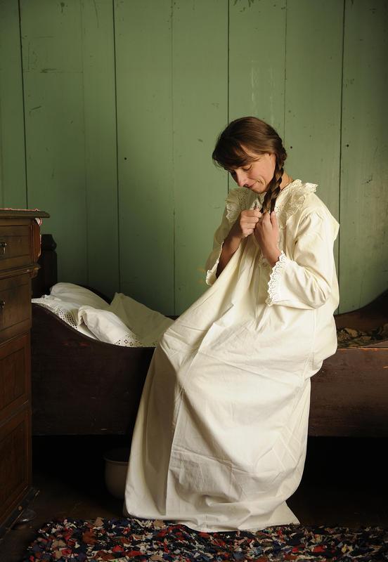 Kvinne med langt hår sitter på sengekanten med en fotsid, hvit nattkjole og fletter håret sitt. (Foto/Photo)