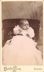 atelierfotografi av eit lite barn i kvit kjole/dåpskjole?