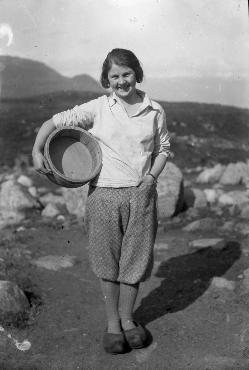 Kvinne i jumpers og knikkers med tresko på føtene og logga trebutt under armen.