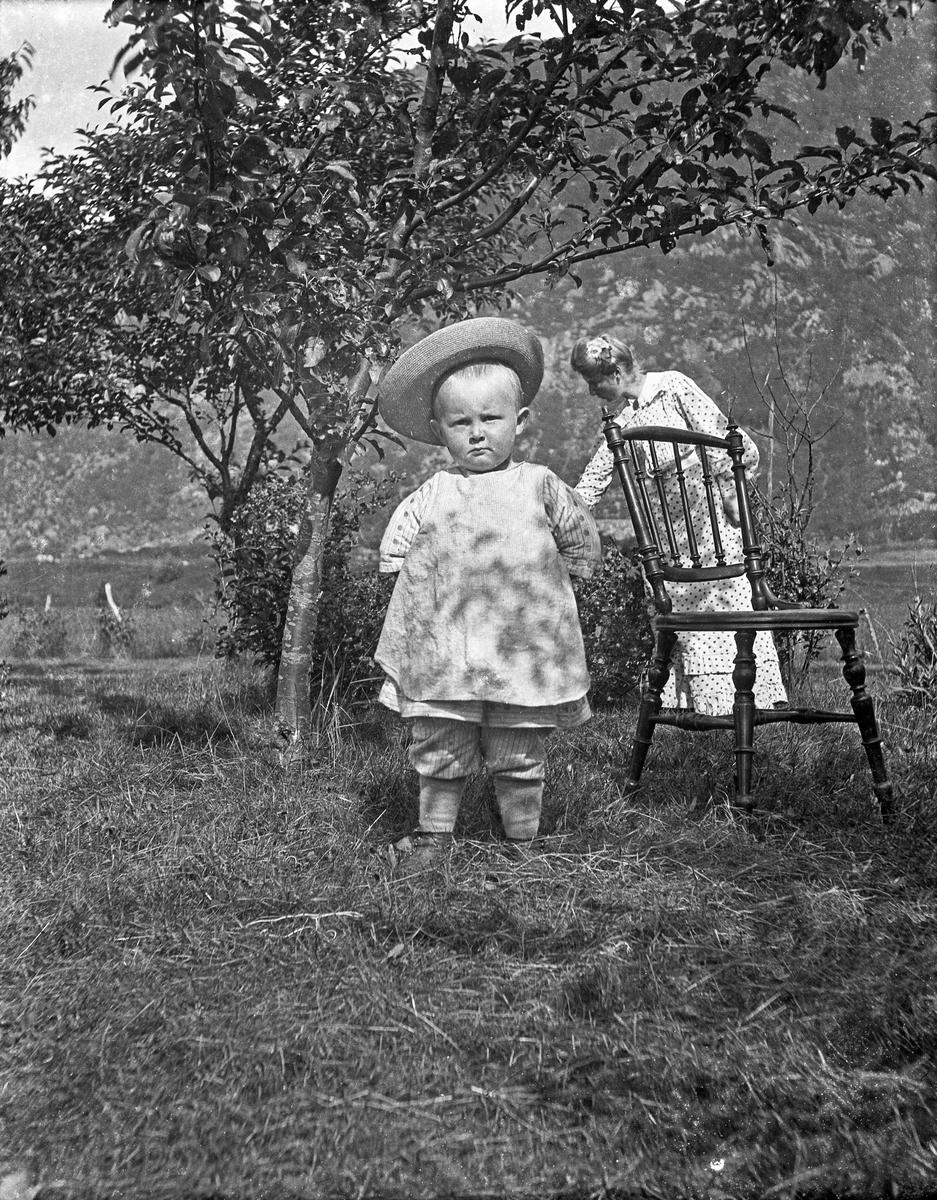 Gruppebilde. En liten gutt står utendørs på plenen ved siden av en trestol, foran et fruktre. Ung kvinne bak stolen. Fjell i bakgrunnen.