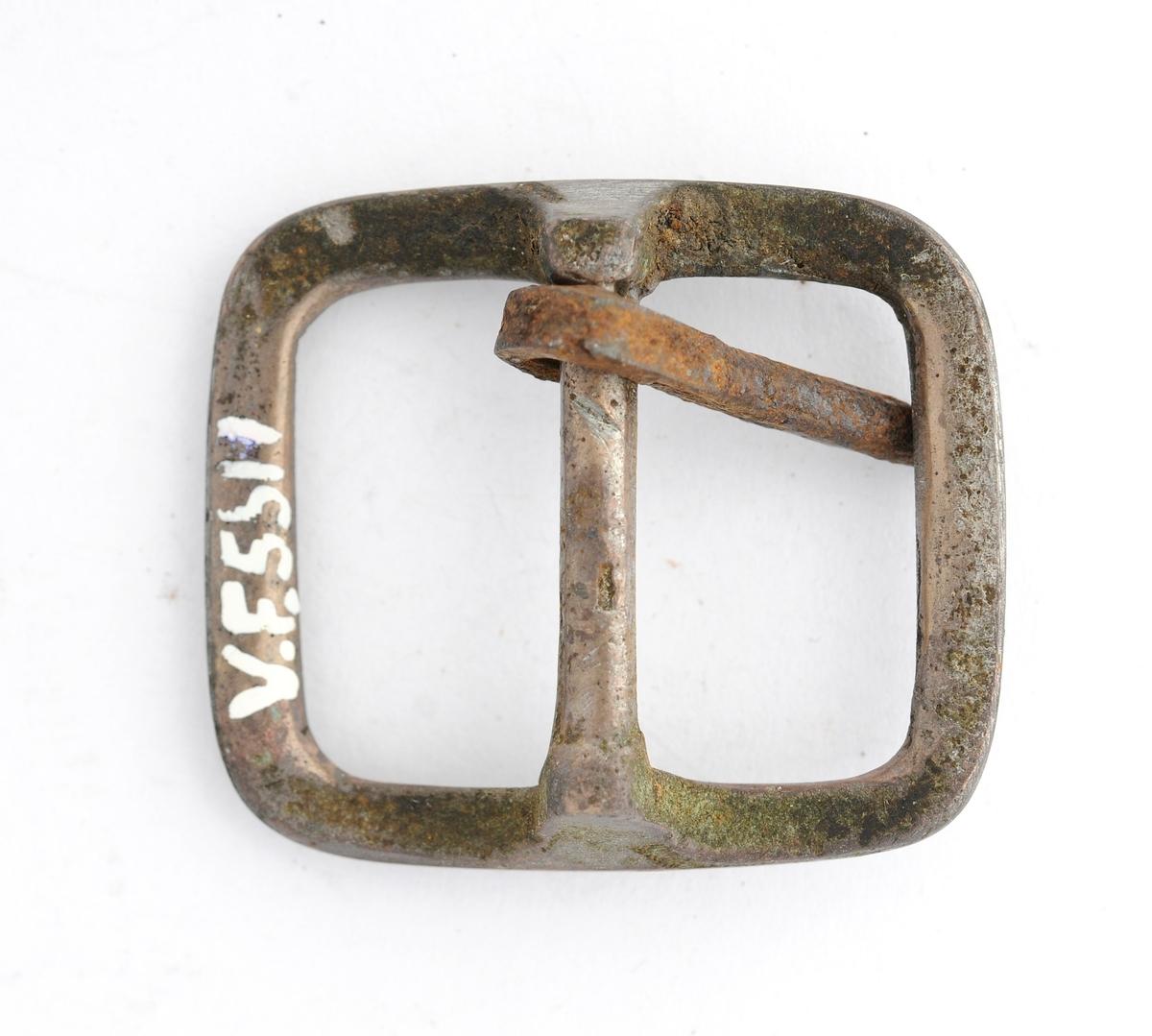 Spenne støypt i messing. Rektangulær form. Tann i jern er smidd rundt stolpen på midten.