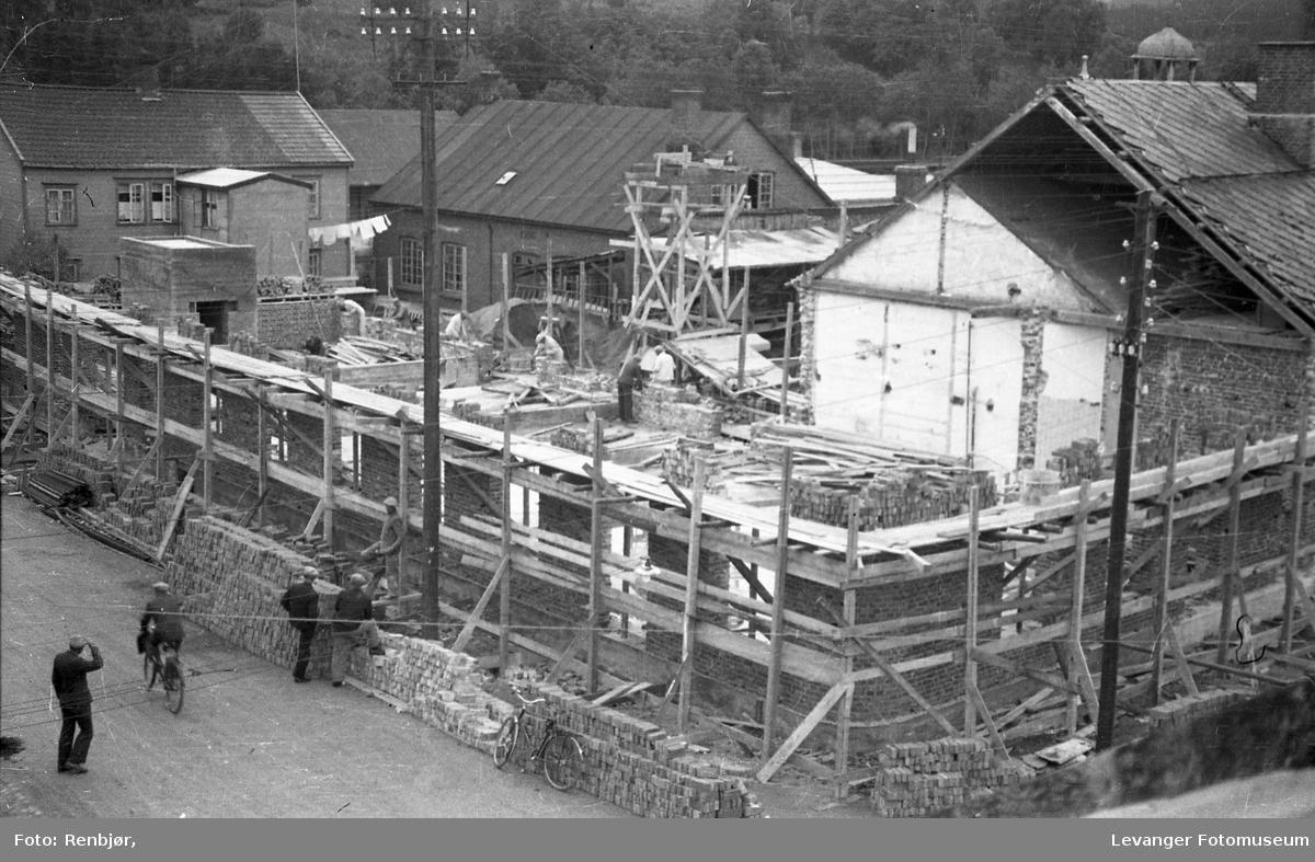 Bygging av nytt meieri i Brugata, vi ser forskalingen til mursteinsbygget, noen menn studerer fremdrifta fra sidelinja.