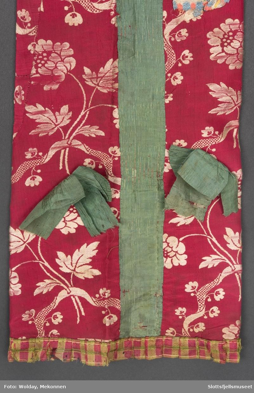 Posen er formet som en ganske smal pose med midtsøm med har rektangulær grunnform med splitt for hodet og sydd sammen ved issen. Den er ikke sydd sammen nederst.  Stoffet er rosa silkerips med hvit lansering (eller rød silkebrokade med lys gult blomstermønster), den er fôret med blått/hvitt stripet og prikket blåtrykk (trykt bomullslerret og en liten bit med mørkeblått bomullsstoff med hvite prikker). Posen bærer tydelig preg av å være omsydd av eldre stoff med mange små biter. I nakken er overskuddet av stoff lagt i små legg rundt et ovalt innfelt stykke av hovedstoffet. Den er dekorert med påsydde silkebånd. Langs halsåpningen er det påsatt et blåsjattert silkebånd. Midt framme, nedover posen er det påsatt et grønt moirebånd. Tilsvarende bånd er også brukt til rosetter. Langs nederkanten er det sydd på et rød- og grønnrutet silkebånd. To sløyfer av samme stoff er festet på hver side av båndet. Langs nederkanten er påsydd et rutete silkebånd i grønt/ rødrosa. To lyseblå silkesløyfer er påsydd ved isseåpningen, samt et mørkeblått med hvit kanter langs hetteåpningen. En tredje pyntesløyfe er hvit med rosa og blå kanter.
