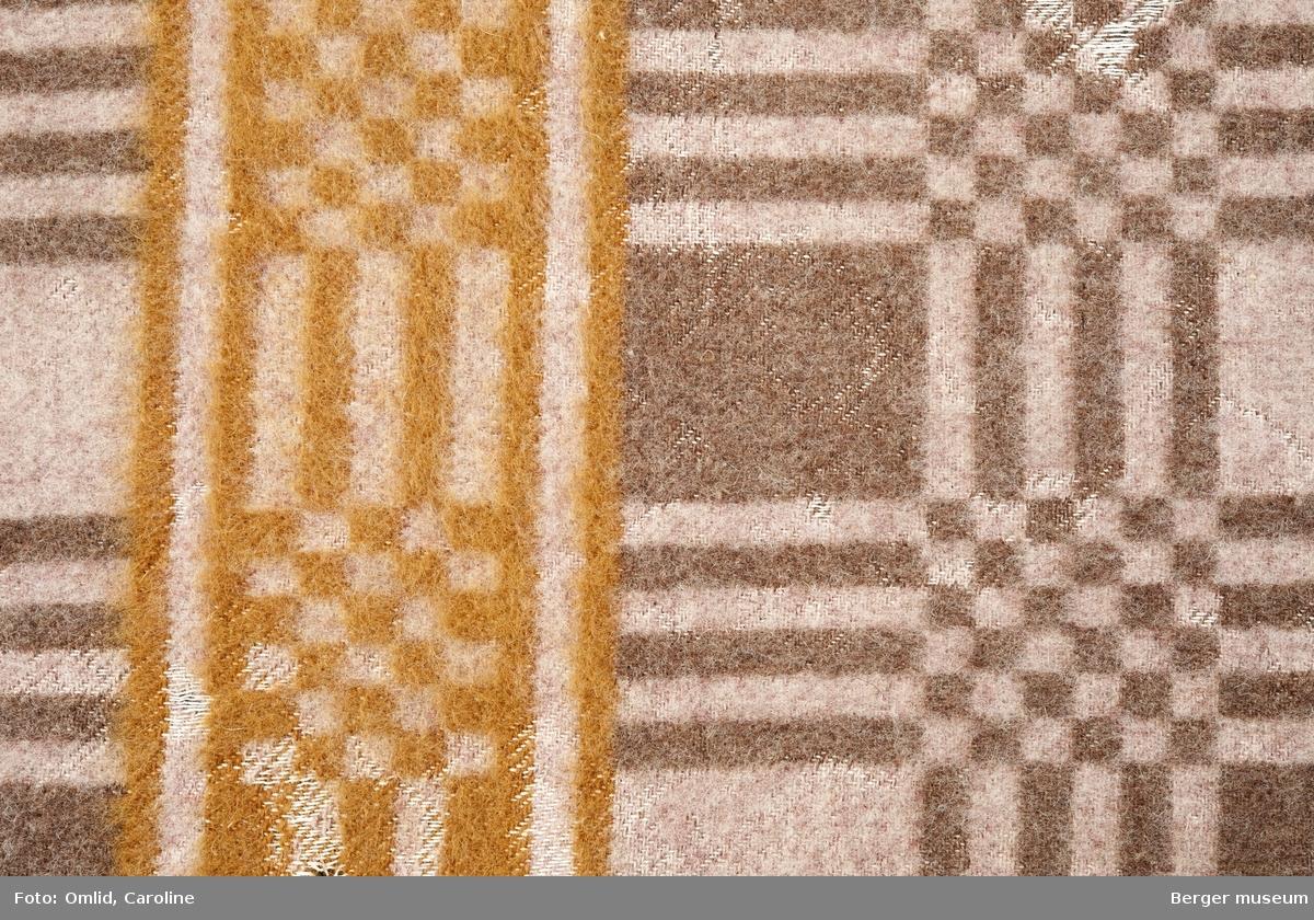 Teppe med geometrisk rutemønster i brune nyanser. En tverrgående bord med samme mønster, men i en rødbrun farge.