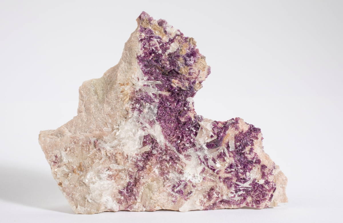 Manganaxinitt (fiolett med kalsitt(?) på finkornet feltspat-kvartsbergart.