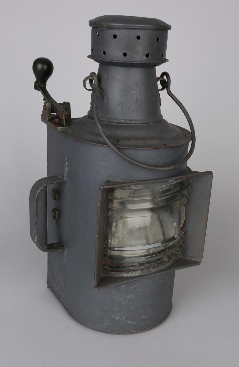 Morselanterne med to håndtak på side og hank på toppen, samt en morsenøkkel til bruk ved signalisering. Med løs parafinbrenner inni.