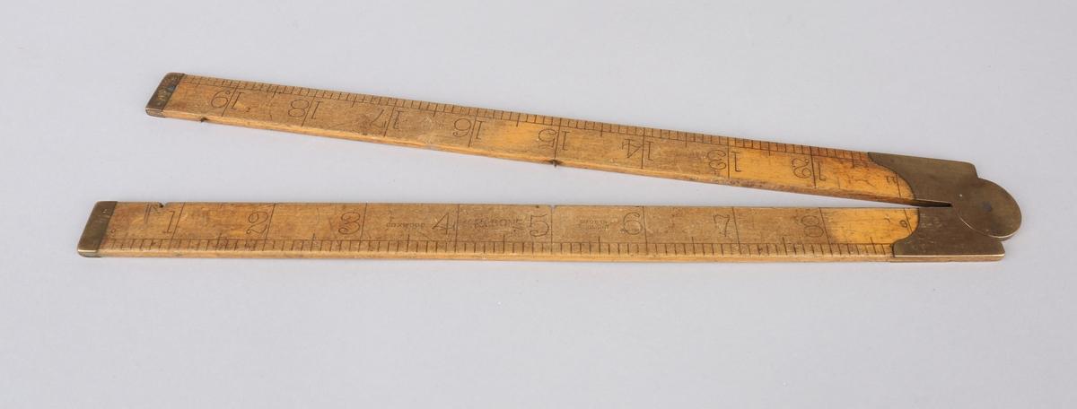 Målestav i to deler med messingbelsag på midten. Måler på begge sider. Total lengde  er 61 cm. som tilsvarer 24 tommer.