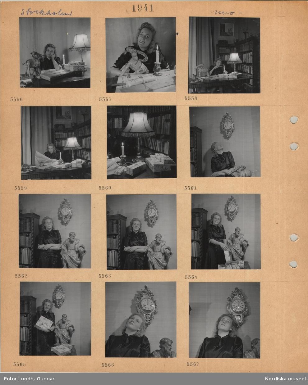 Motiv: Stockholm, modell i klänning som poserar, sitter vid bord med inslagna julpaket, tänt stearinljus, bordslampa, halmbock, slår in paket, lackar paket, står vid ett väggur, skulptur.