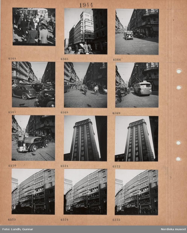 Motiv: Gata med fotgängare, trådbuss, cyklist, varuhusets PUB fasad, gata med stenläggning, bilar, butiker, trafikljus, bil med gengasaggregat, fasaden på ett av Kungstornen, fasad på affärs- och kontorsbyggnad.