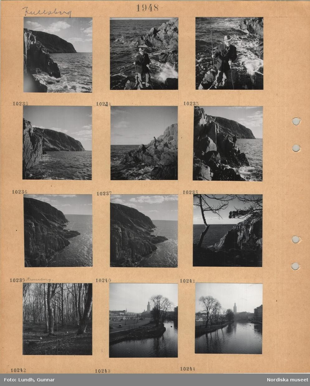 Motiv: Kullaberg, en man fiskar med spö från klippig strand, man med fångad fisk och kastspö, klippor och tallar, bokskog med löv på marken, Stockholm, strandkant vid kanal, bilar, i bakgrunden stadshuset, träd, bostadshus.