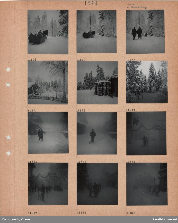"""Motiv: Tällberg, hästdragen släde med passagerare på väg, två promenerande män med käpp, timmerbyggnad, trägärdsgård, snöiga träd, stor vedstapel utomhus, brunnsvev i snö, gående person med skidor på axeln, man med sparkstötting på väg, bytorg i snö med julgran, midsommarstång, girlanger, man med transportcykel, bygata med biltrafik, gående, person på skidor, girlanger och skylt """"GOD JUL"""", butiksskyltar, kvinna med sparkstötting."""