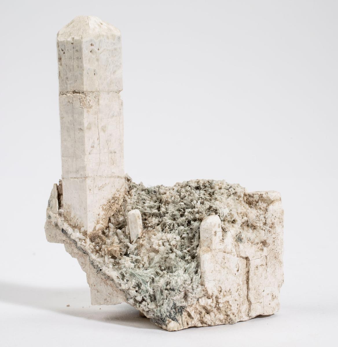Hvit apatitt (CaOH?) krystall på matriks (reparert) av apatitt, albitt? (mikrokryst. hvite) og aktinolittasbest. Diopsidforekomst.
