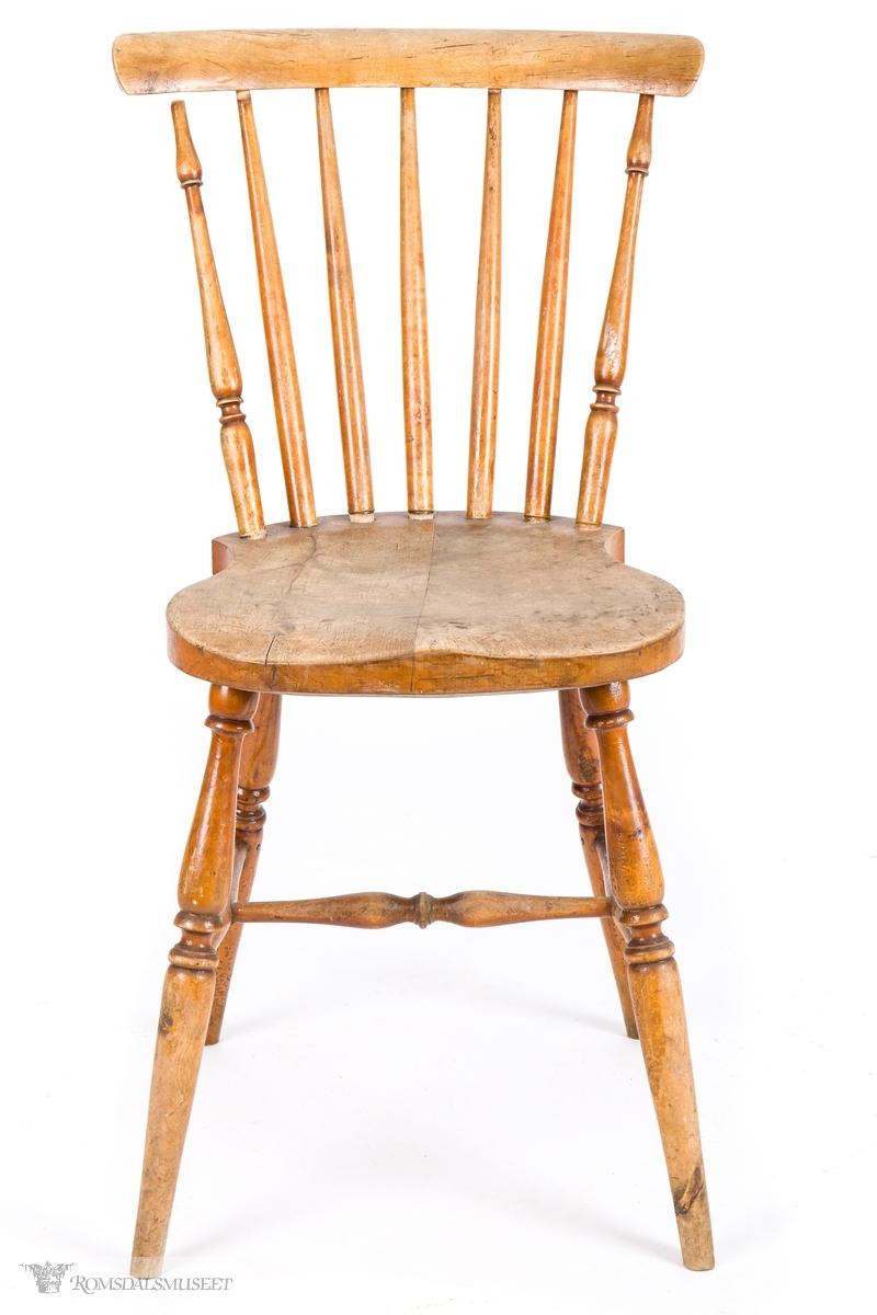 """Pinnestol eller """"Jønkjøpingstol"""" med kraftig skjoldformet sete med dreide ben med H- sprosse imellom. 7 pinner i ryggen, der de ytterste har dreide mønster, som går inn i et buet skulderbrett."""