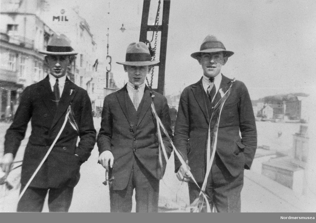 3 gutter på Vågekaia (Piren) Kristiansund rundt 1930. Russ; se bambusstokkene. 17.mai-sløyfer. Konfirmantklær. Nordmøre museums fotosamling