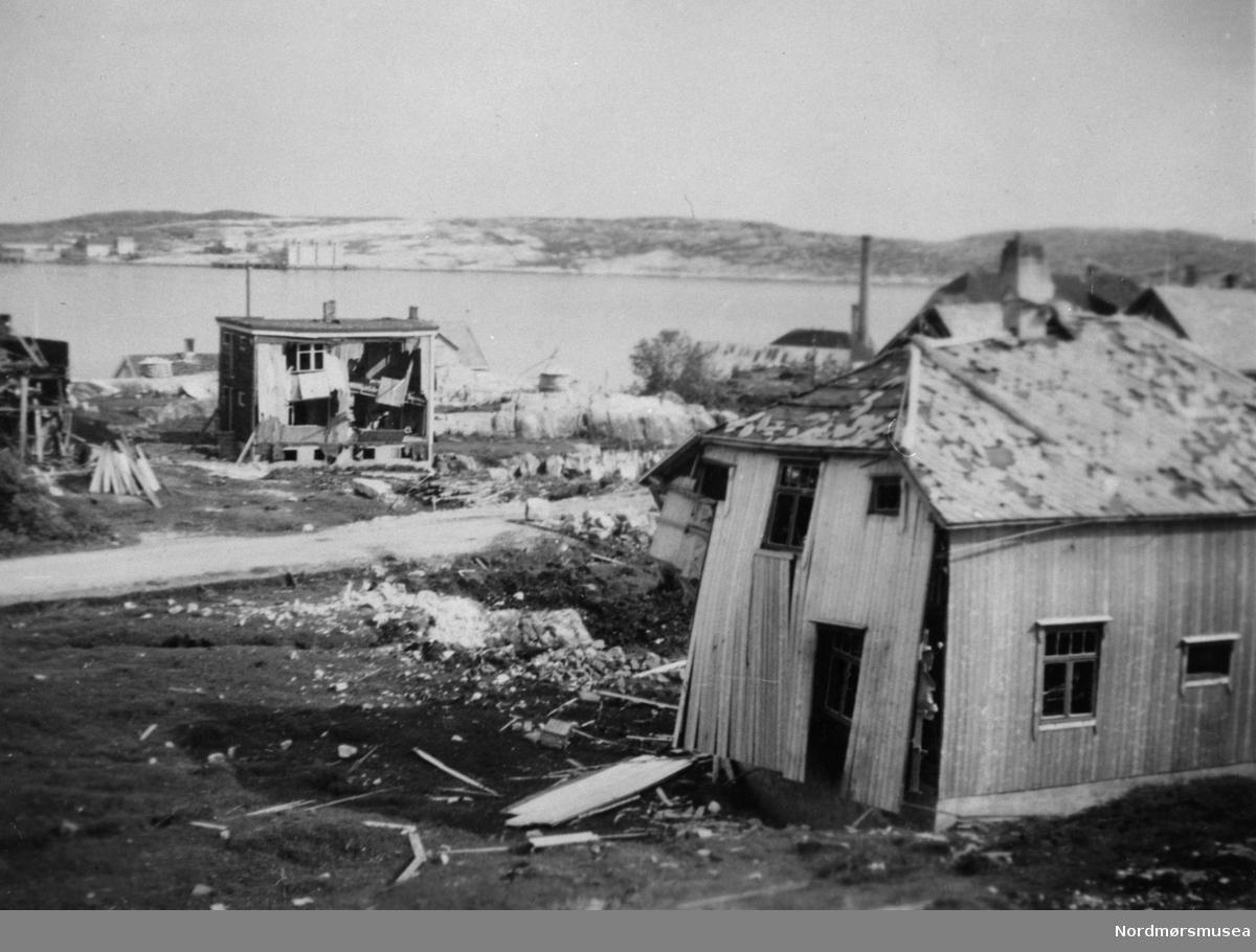 """Ødelagte hus etter sprengbomben på Dahle i Bremsnes ved Kristiansund, 28. april 1940. I forgrunnen skimter en tomten og området hvor 4 mennesker ble drept. De drepte var Peder Gaupset, Kristian Gundersen, moren i Ohrvikhuset Olga Ohrvik og sønnen Asbjørn Ohrvik. Det ødelagte huset i front tilhørte familien John Sund. Til venstre for Sunds hus ses huset til familien Melvin Ingebrigtsen og helt til venstre ses en bit av det ødelagte Hollekimhuset. Mellom Hollekimhuset og Ingebrigtsenhuset ses taket på huset til familien John Bakken, og til høyre for Ingebrigtsenhuset ses taket på huset til familien Kristian Stabben. Bak Ingebrigtsenhuset ses klippfiskbergene, nedre Amundbergene, med klippfiskla. Over taket, og bak skorsteinen, på Sundhuset, ses taket på huset til familien Peder Moen og til høyre for Moenhuset ses taket på huset til familien Liabø. Bak, og over taket på Moens og Liabøs hus, ses """"Murgården"""", Storviks Mek. Verksteds leilighetshus, og til venstre for det ses kobberslagerverkstedsbygget med den høye skorsteinspipen. Daleveien ses som en grå stripe på bildet. I bakgrunnen ses Skorpa og Visnesbrygga. På veien opp til Persløkka er det satt opp en minnetavle med navn på drepte etter bombingen. Bildet er fra 1940.  (P A Storvik) -- Dale med Skorpa bak, serie. Kristiansund bombet. 2. verdenskrig. Nordmøre museums fotosamling."""