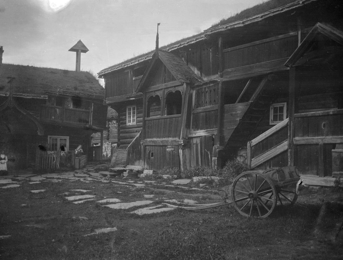 Gammelt gardstun, to store tømmerbygninger med svalganger, klokketårn, bikk-kjerre