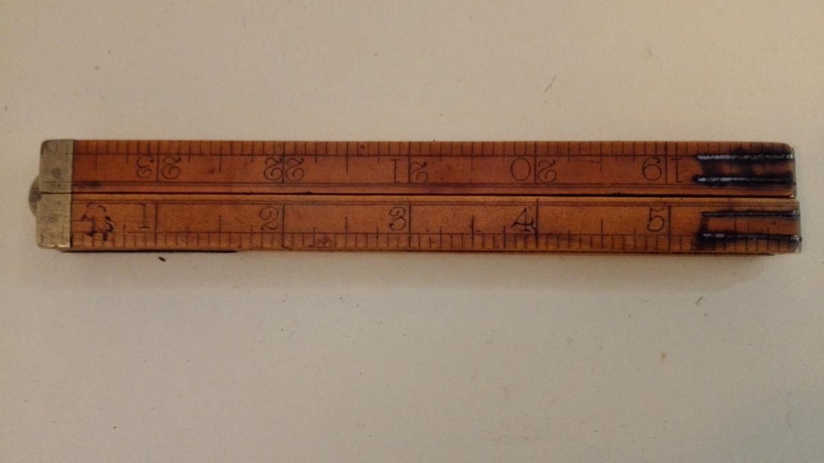 """Samanleggbar tommestokk med fire ledd, Stokken er 24 tommar, dvs 1 alen. Dette er """"norske"""" tommar (etter lov av 1824) på 2,615 cm. Kvar tomme er delt inn i 12 deler, kalla """"linjer"""" eller """"strå"""". Tommestokken er reparert med eit jarnbeslag."""