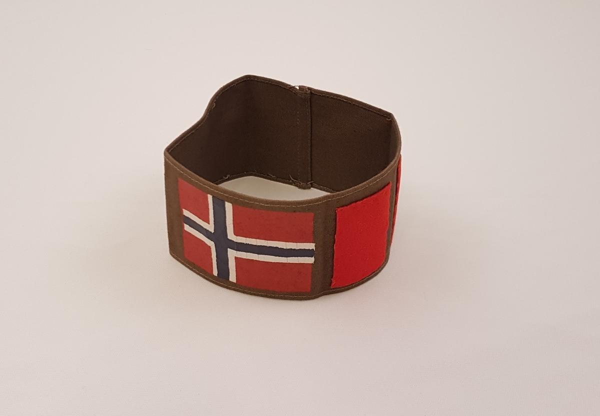Brunt armbind påmalt et norsk flagg og påsydd en bred og en smal rød stolpe.