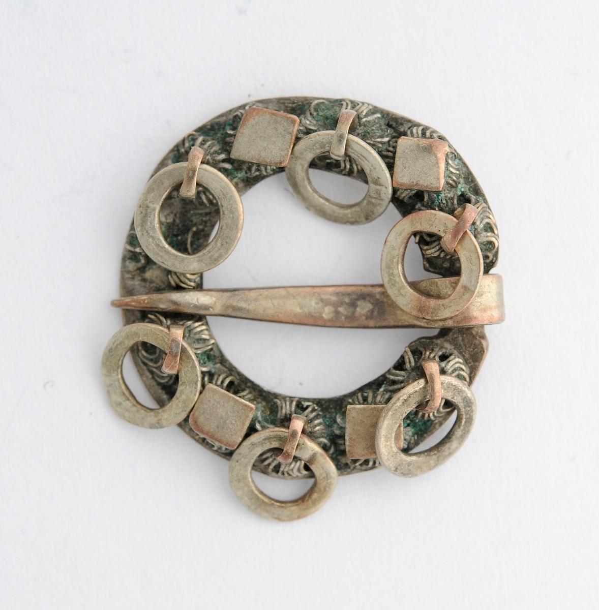Sølje, halsring i messing (forsølva?). Sirkulær, støypt, med 11 krusar og seks ringar på framsida. Ei nål (tann). Glatt på baksida.