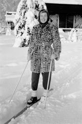 Kvinna i päls på skidor