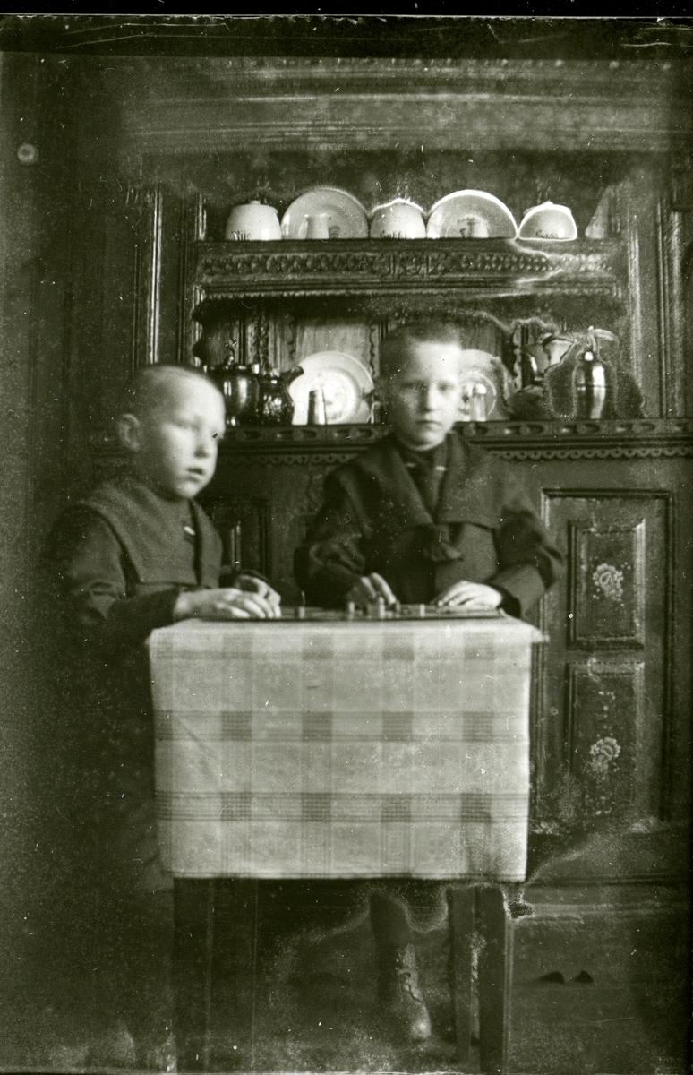 To gutar sit ved eit bord og spelar spel. Olmhusskåpet i bakgrunnen.