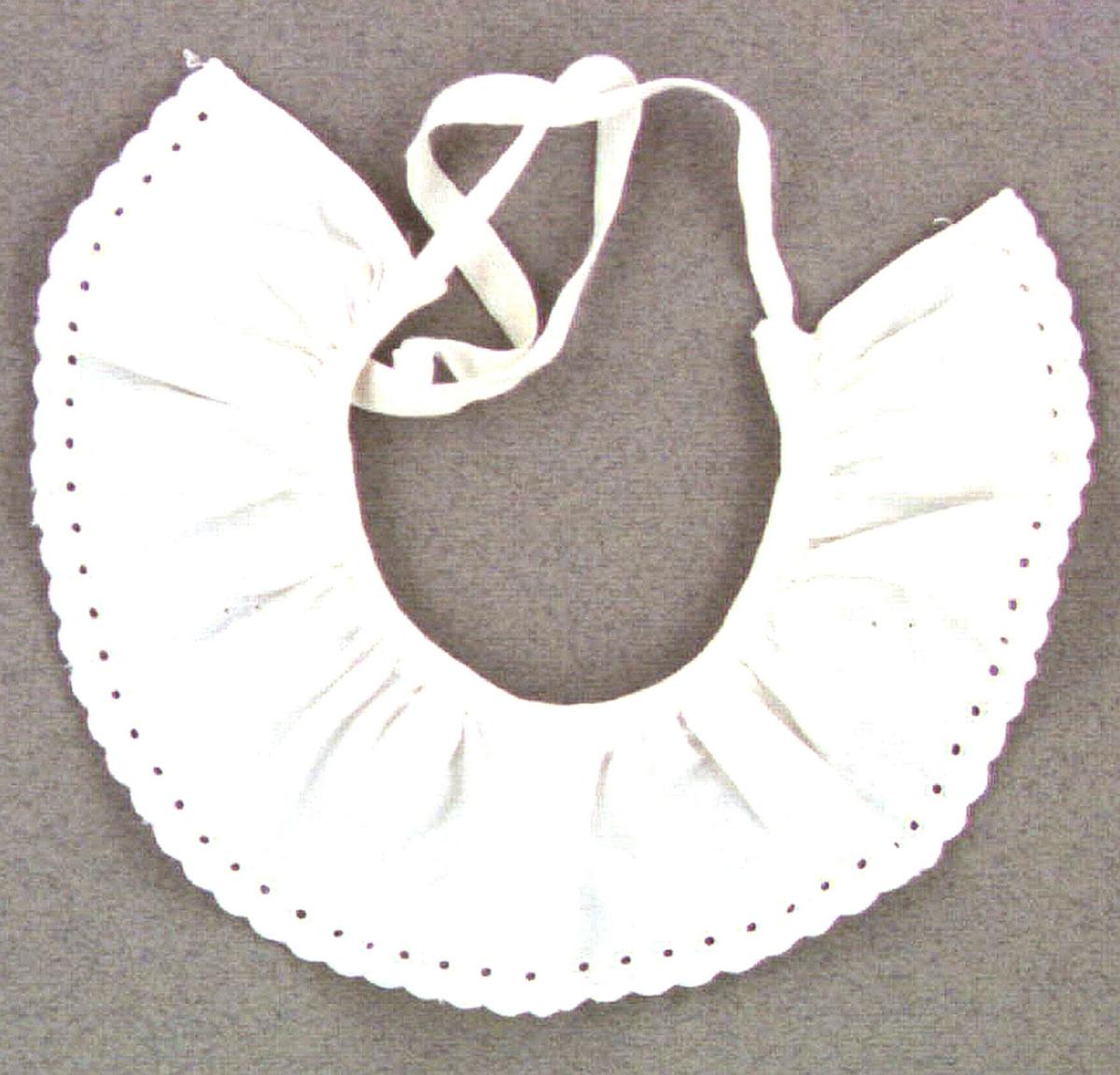 Dockkrage av vitt bomullstyg med brodyr. Knytes med två bomullsband.