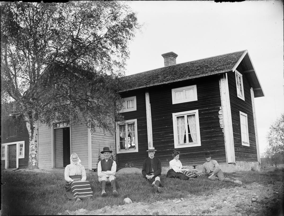 Män och kvinnor i folkdräkt, sitter i gräset framför bostadshus, Dalarna