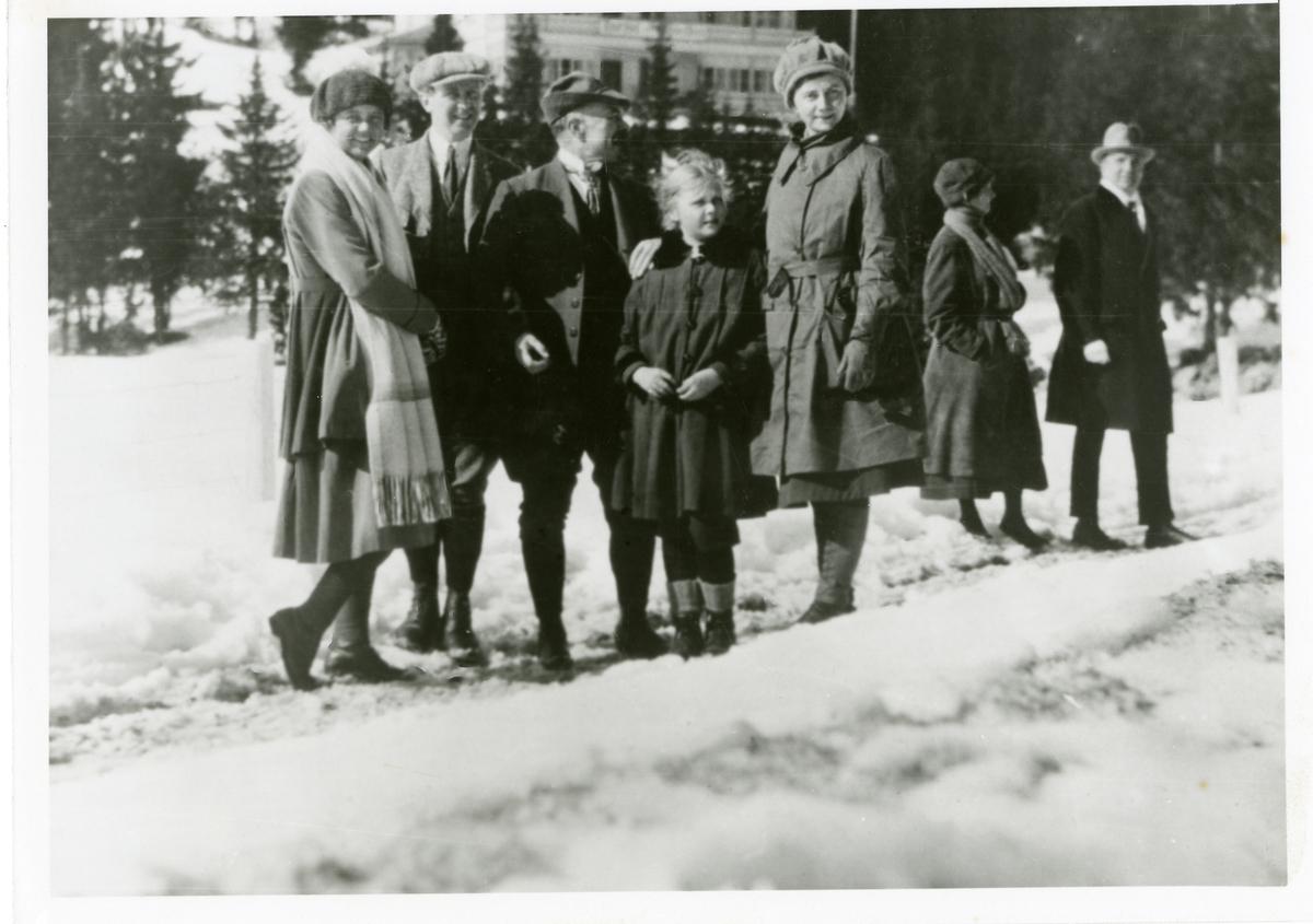 Ein familie står utanfor eit stort hus. Det er vinter og snø ute.