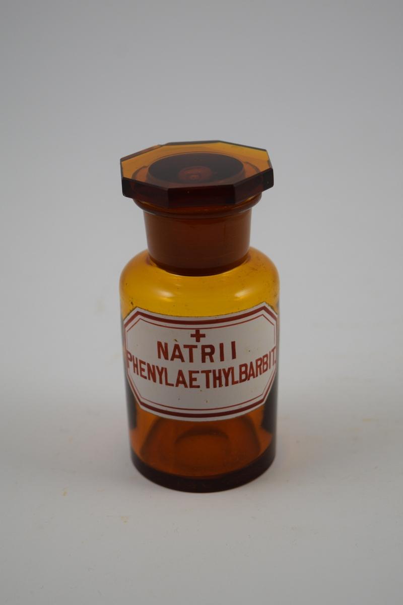 Brun glasskrukke med glasspropp. Etikett hvit med rød skrift. Ett kors, betyr giftig: enkorsgift. Har inneholdt Nartii Phenylaethylbarbit - brukes som sovemedisin og beroligende.