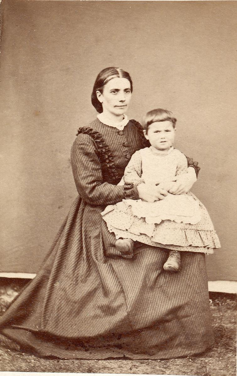 Portrett. Mor og datter. Fru baker Pedersen med datteren Nanna på fanget.