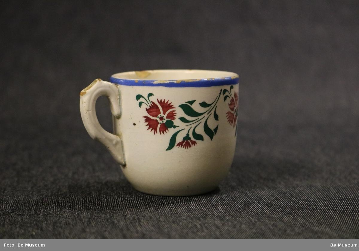 Blå rand langs topp av koppen. Rankemotiv som består av blomstrar og bladverk under munningsranda.