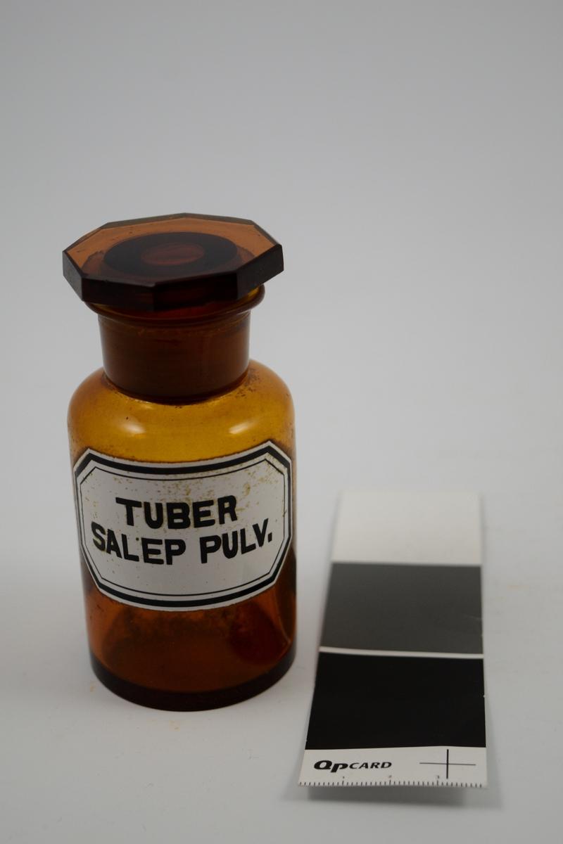 Brun glasskrukke med glasspropp. Hvit etikett med sort skrift. Tuber Salep pulv. ble brukt til legemiddelproduksjon. Fortykningsmiddel.