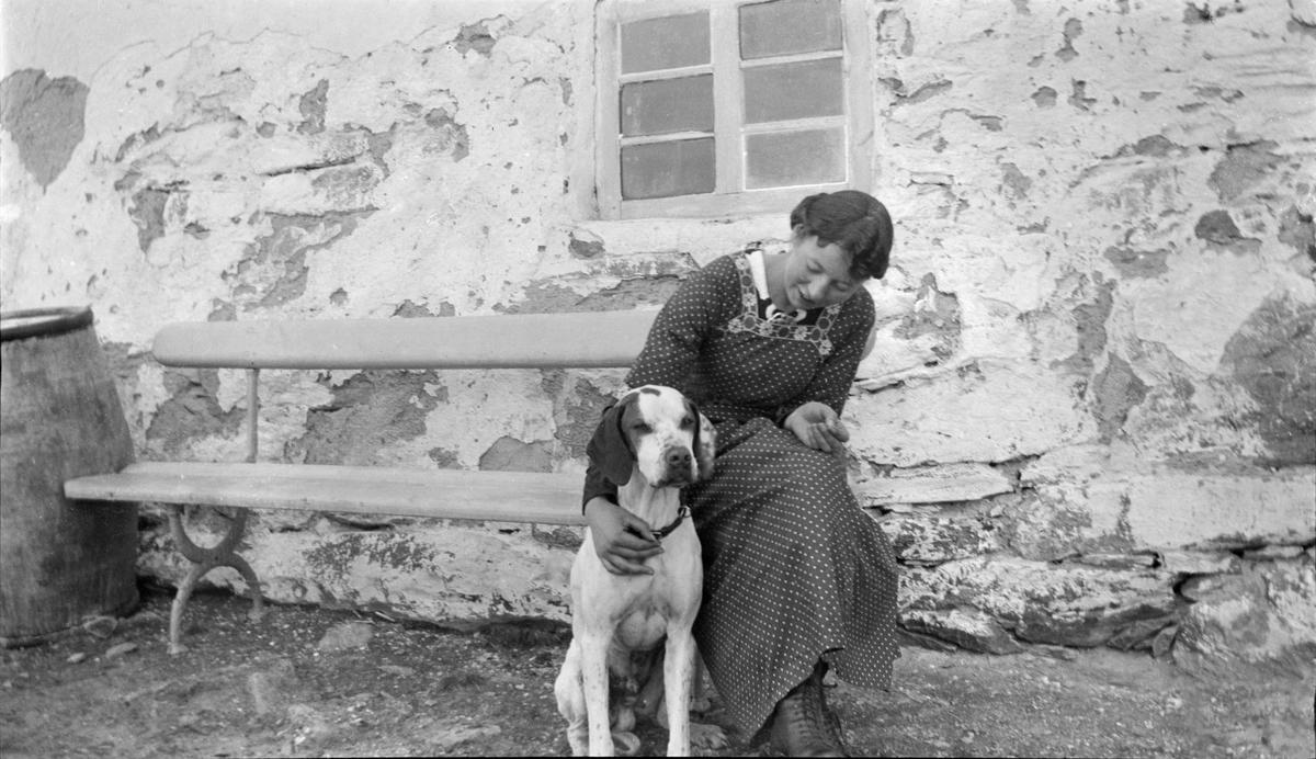 Kvinne på benk med hund.