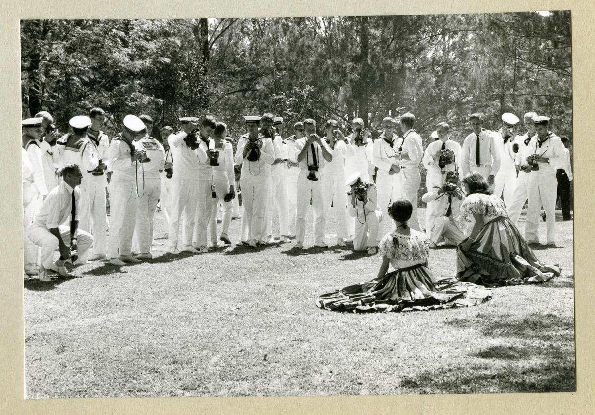 Bilden föreställer två kvinnor i lokala kläder som sitter på en gräsmatta i Puntarenas medan besättningsmän i vita uniformer från minfartyget Älvsnabben står framför och tar kort. Bilden är tagen i samband med fartygets långresa 1966-1967.