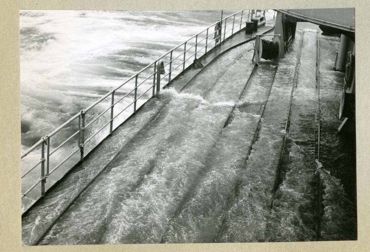 Bilden föreställer minfartyget Älvsnabbens däck fyllt med vatten till följd av stormigt vatten i samband med orkanen Diana. Bilden är tagen under fartygets långresa 1966-1967 i Tasmanska sjön på väg mellan Sydney och Wellington.