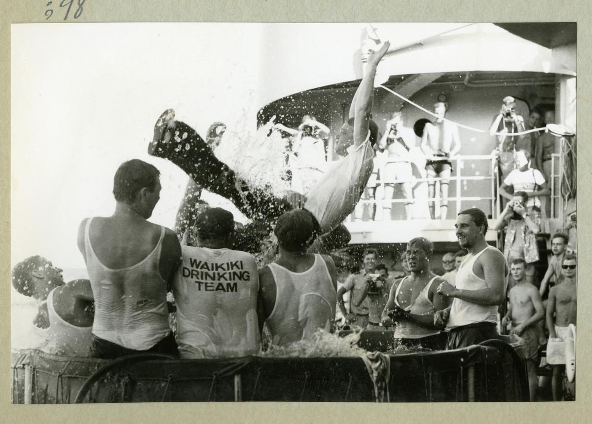 Bilden föreställer flera besättningmän i en liten vattenbassäng ombord på minfartyget Älvsnabben. I bakgrunden syns ytterligare besättningsmedlemmar som åskådare till badet. Bilden är tagen i samband med fartygets långresa 1966-1967.