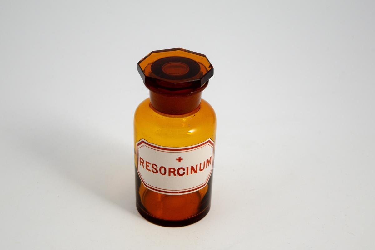 Brun glassflaske med glasspropp. Hvit etikett med rød skrift og ett kors, betyr at innholdet er giftig. Resorcin ble brukt i linimenter og kremer mot vorter og kviser og andre hudlidelser. Til bruk i legemiddelproduksjon.