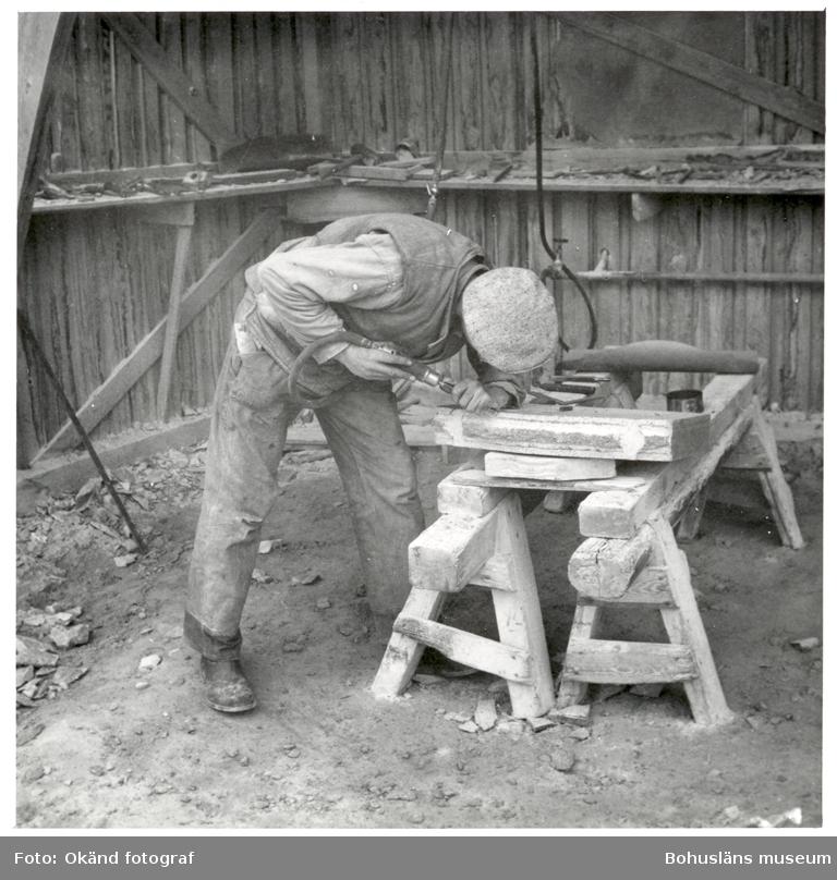 Stenhuggare som mejslar fram kantprofil på stenblock