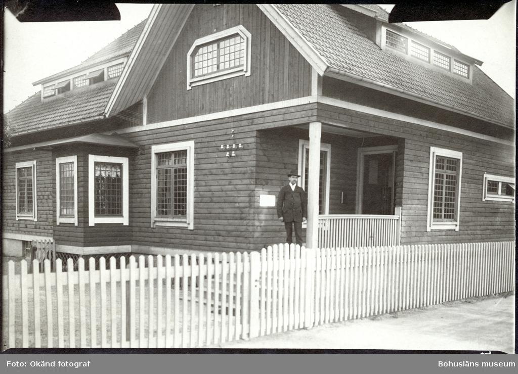En man står på en veranda på ett stort hus med staket runt om