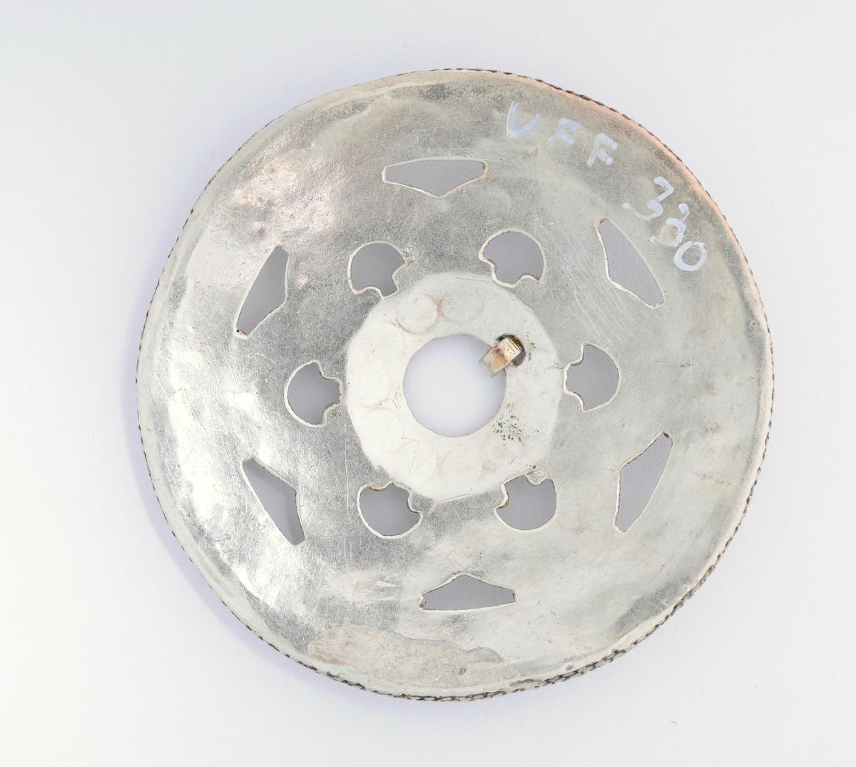 Sølje, slangesølje i sølv (utan stempel). Filigransarbeid på gjennombroten rund plate. Forgylt. Ei liten rund opning i midten med ei tann (nål). Glatt bakside.