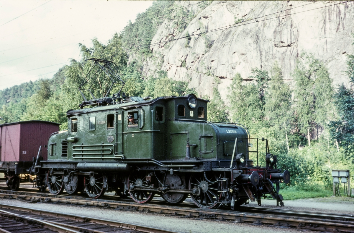 Godstog retning Kristiansand på Grovane stasjon. Toget trekkes av elektrisk lokomotiv type El 1 nr. 2004.